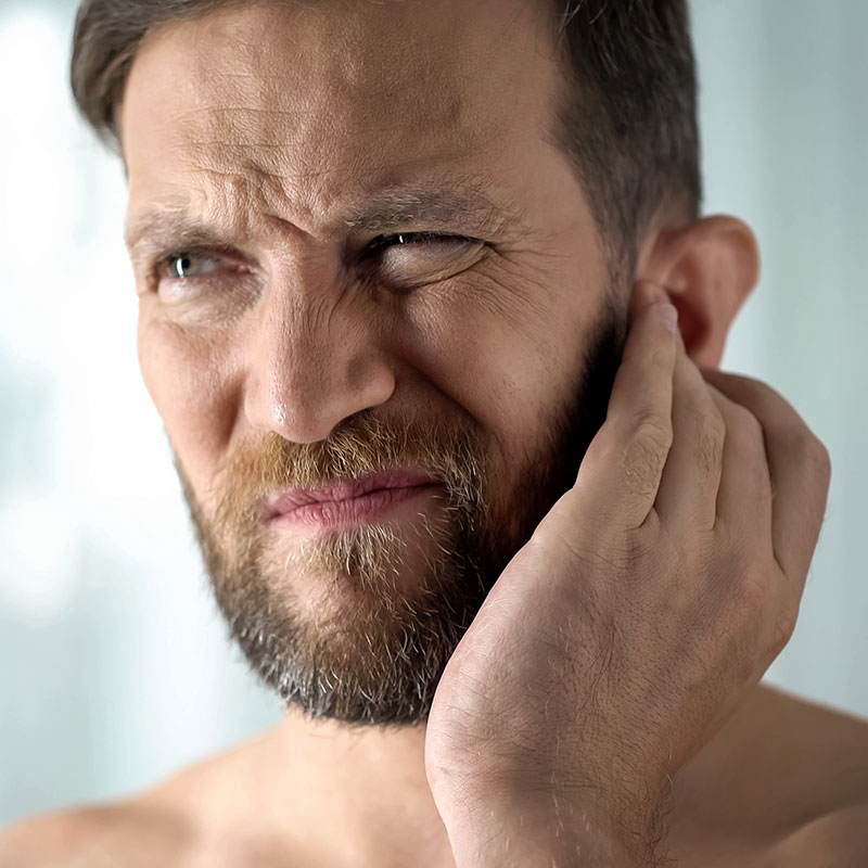 Man holding ear because he has hearing loss and needs hearing aids.
